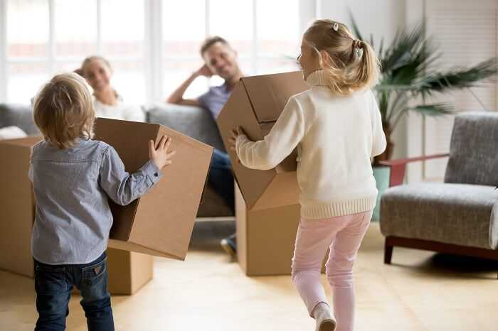 Kids are playing with moving boxes in front of their parents