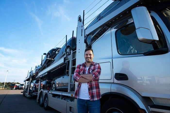 Professional smiling truck driver transporting cars